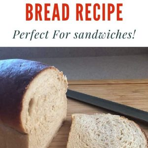 Loaf of bread with a slice cut off it. The knife is sitting next to the loaf. There is a text overlay that says 100% whole wheat bread recipe: perfect for sandwiches at the top.
