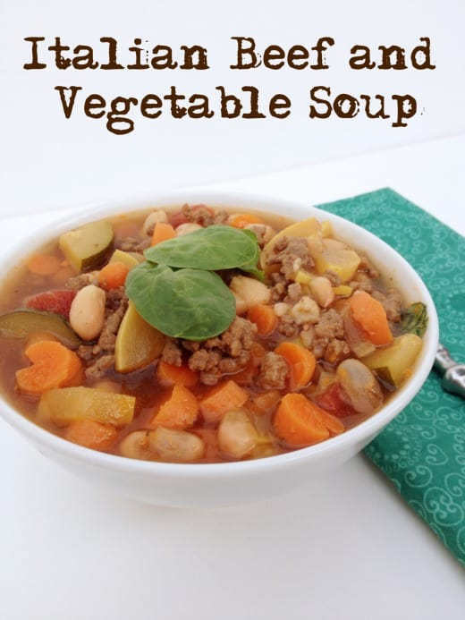 white background with white bowl of italian beef and vegetable soup. soup has carrots, white beans, ground beef, zuchinni and yellow squash in it. Has text overlay that says Italian Beef And Vegetable Soup.