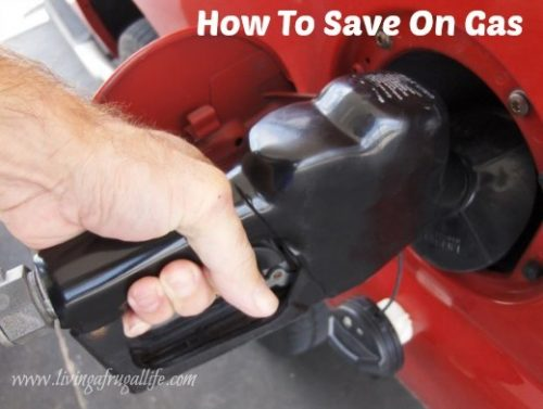 male hand putting gas in red car with a gas pump.