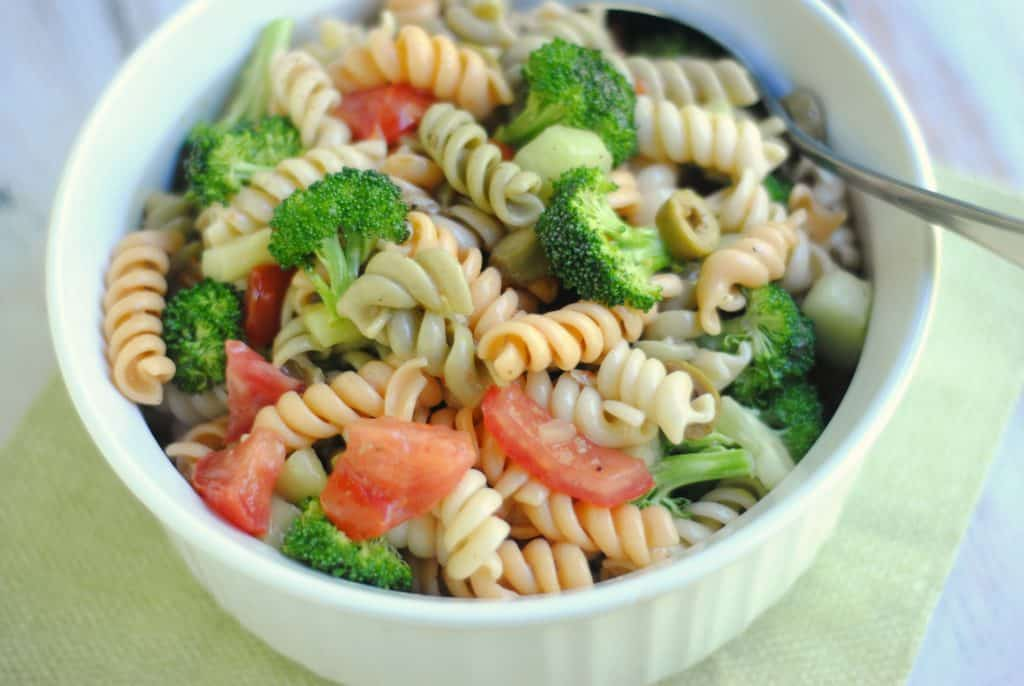 white bowl on a green napkin background filled with an Italian Broccoli and Pasta Salad of tri color pasta mixed with broccoli, tomatoes, and peppers. There is a spoon on the right.