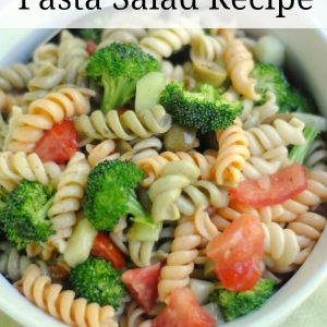 white bowl on a green background filled with tri color pasta mixed with broccoli, tomatoes, and peppers. There is a text overlay that says italian broccoli and pasta salad recipe.